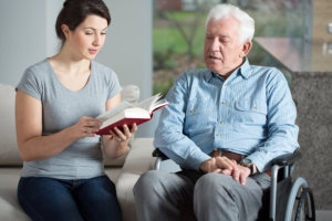 caregiver reading a book to her patient